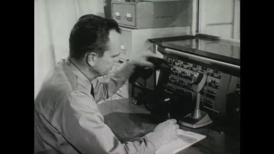 UNITED STATES: 1950s: man answers phone at switchboard. Siren warning system.