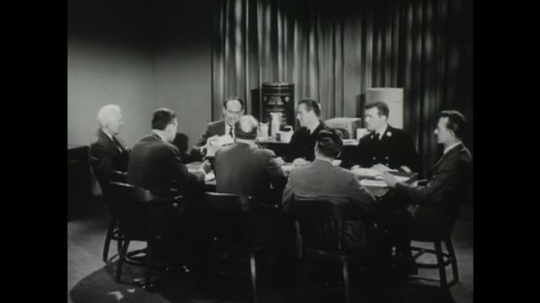 UNITED STATES: 1950s: men talk at planning meeting.