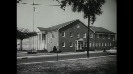 UNITED STATES: 1950s: municipal building in street. Fallout shelter symbol on wall.