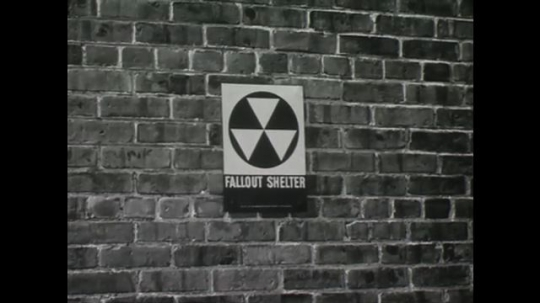 UNITED STATES: 1950s: Fallout shelter symbol on wall of building. People in meeting
