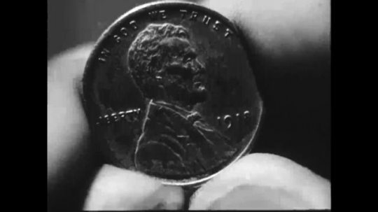 UNITED STATES: 1940s: American coin in hand. Man stares ahead. Man smiles. Statue in Washington