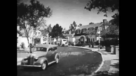 UNITED STATES: 1940s: car drives along street. Soldiers in truck. Buildings on horizon.