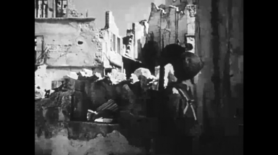 UNITED STATES: 1940s: Italian city after bombing. Soldier stands in street. Poster of soldier on wall.