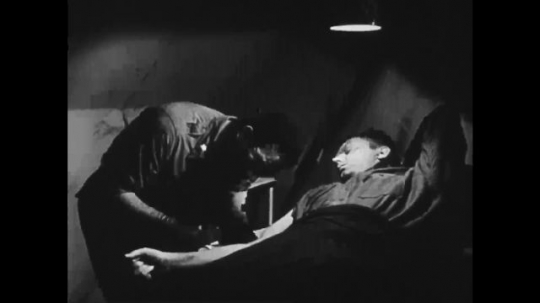 UNITED STATES: 1940s: medic cares for soldier in military hospital camp
