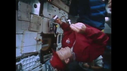 UNITED STATES: 1990s: astronaut on space shuttle eats food. Animation of space shuttle in free fall. Astronauts experience microgravity