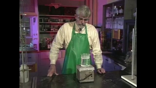 UNITED STATES: 1990s: man watches as fluid heats up on stove.