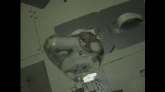 UNITED STATES: 1990s: liquid forms sphere in microgravity environment. Astronaut plays with water in space.
