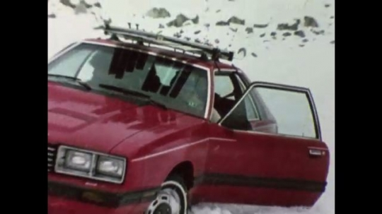 United States: 1980s: Teenagers get out of car stuck in snow. Driver gets into car.