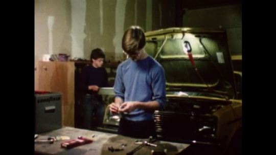United States: 1980s: teenagers work on car in garage. Hands fix spark plug. Boy opens can of oil.