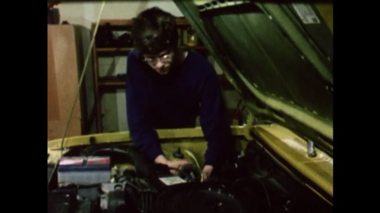 United States: 1980s: boy pours oil into car engine. Close up of tin. Hand uses wire brush to clean car engine. Hand uses cloth to wipe engine of car.
