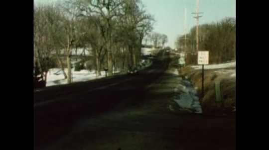 United States: 1980s: car drives along country road. Car drives along motorway. Poor visibility on motorway.