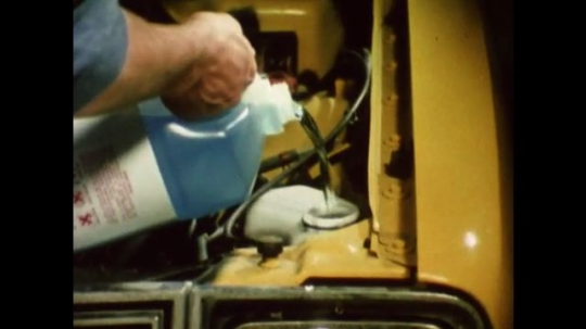 United States: 1980s: hands pour windscreen wash into car