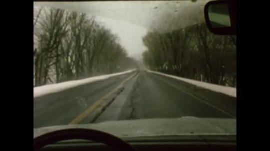 United States: 1980s: View of road through car windscreen. Lorry approaches car on road. Finger presses wash wipe button on car dashboard. Wipers move on car windscreen