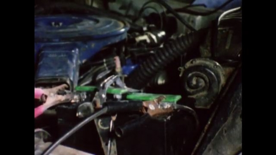United States: 1980s: pliers touch car engine and start fire and explosion. Lady signals for car to stop. Lady picks up clips.  Car engine stops. Lady attaches jump leads to battery.