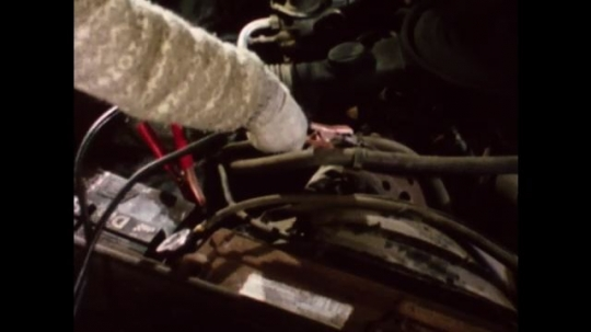 United States: 1980s: hand attaches jump leads to car battery. Lady inspects jump leads on battery. Engine of car starts. Lady jump starts car.