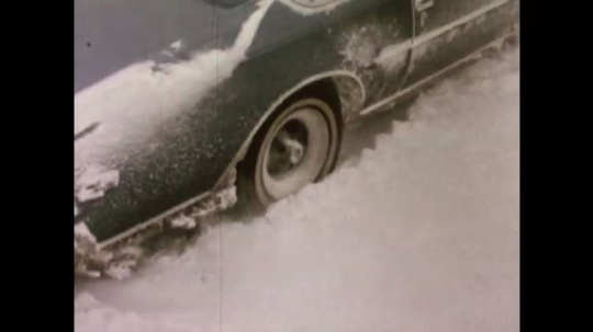 United States: 1980s: car wheel spins in snow. Car stuck in snow. People push car stuck in snow.