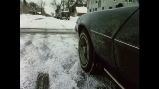 United States: 1980s: car stops at junction. Car drives along snow covered road.