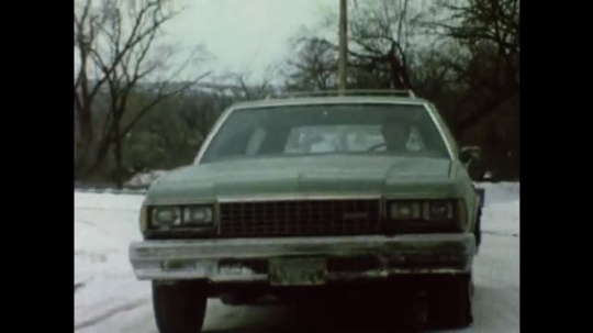 United States: 1980s: car slides on snow on road. Car spins into side of road. Young person drives car in snow. Front view of moving car on road. Car begins to slide on road.