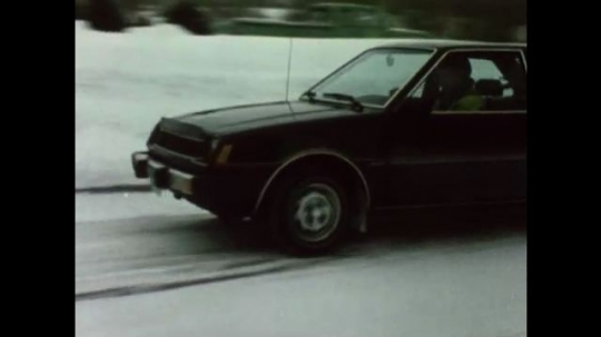 United States: 1980s: car drives along snow covered road. Car starts to slide on snow on road. Car drives over black ice on road.