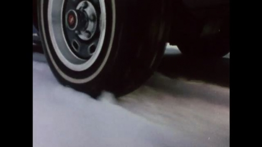 United States: 1980s: close up of car tyres driving across snow on road. Car wheels come to a stop.