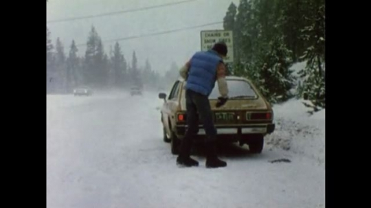 United States: 1980s: Man gets out of car. Man puts snow chains on car tyres. Man wears sunglasses as he drives in snow.