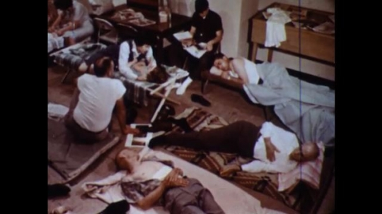 UNITED STATES 1960s: Pan across people on cots, women tending to patients.