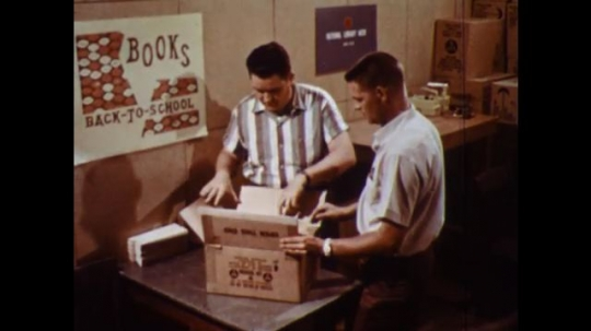 UNITED STATES 1960s: Men open box / Hand flip through instructions.