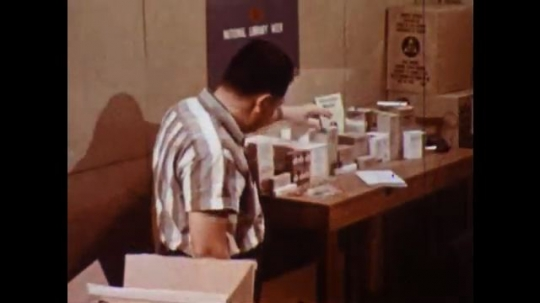 UNITED STATES 1960s: Man looks at drug boxes, picks up booklet / Man looks through booklet.