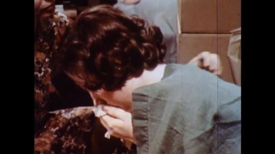 UNITED STATES 1960s: Girl coughing in cot, woman gives girl tissue / Close up, woman feels girl