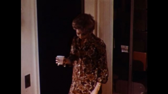 UNITED STATES 1960s: Woman enters with cup, kneels by cot, tilt down to woman drinking water / Woman puts gauze in trash.