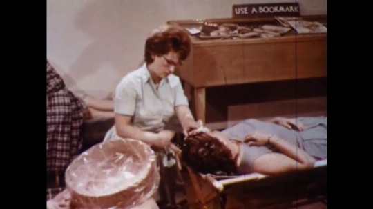 UNITED STATES 1960s: Woman nurses woman in cot, pan to woman giving woman pill / Woman takes pill, lies down.