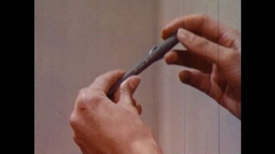UNITED STATES 1960s: Close up, hands remove thermometer from case.