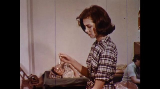 UNITED STATES 1960s: Woman cleans thermometer, walks to woman in cot / Close up, woman takes thermometer in mouth.