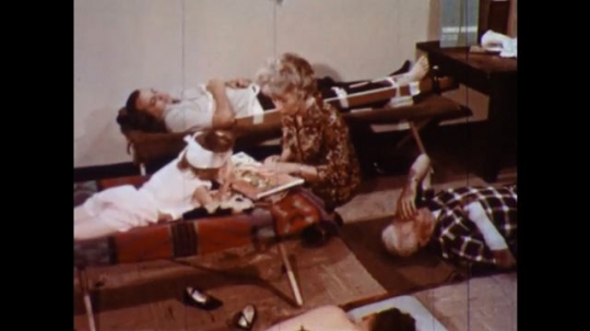 UNITED STATES 1960s: People in cots, woman reads to girl, stands / Woman sits with man, feels man's head.