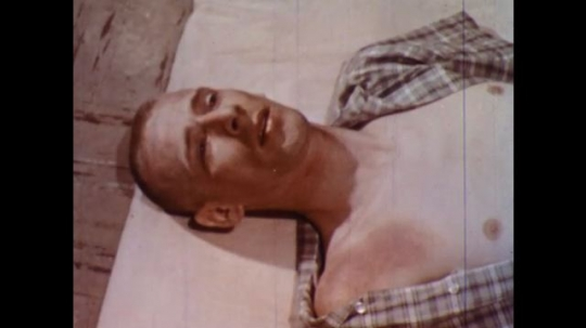 UNITED STATES 1960s: Man lying on sheet, pan to hand holding man