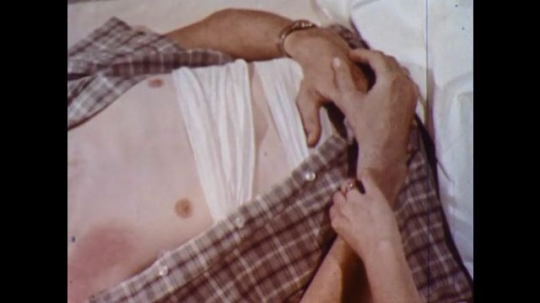 UNITED STATES 1960s: Close up of bandaged chest / Woman taking man