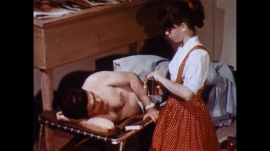 UNITED STATES 1960s: Girl talks to man in cot / Close up, burn on man