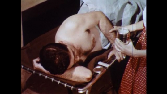 UNITED STATES 1960s: Man lies on stomach, girl puts cream on man