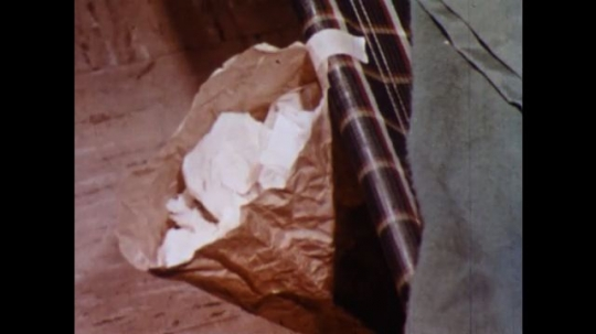 UNITED STATES 1960s: Close up, bag taped to cot, hand puts tissue in bag / Woman puts bag in trash / Woman washes hands.