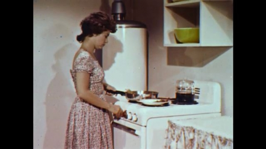 United States: 1960s: lady cooks food on stove. Side profile of woman