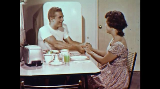 United States: 1960s: man and lady holds hands across breakfast table. Man hugs lady. Lady sees doctor.