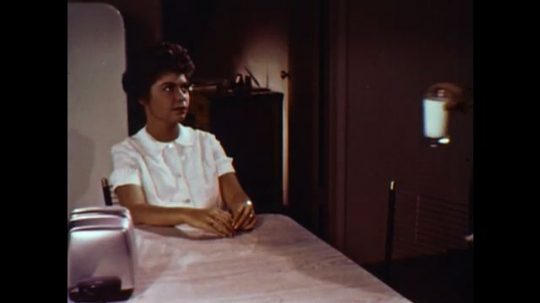 United States: 1960s: sailor brings glass of milk to lady at table. Man and lady talk at table