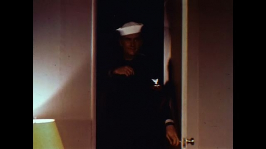 United States: 1960s: sailor arrives home. Sailor kisses wife at door. Lady and sailor talk.