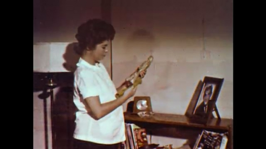 United States: 1960s: lady dusts shelf. Lady looks at photo in frame. Lady walks with friend. Doctor weighs lady. Women arrive at church