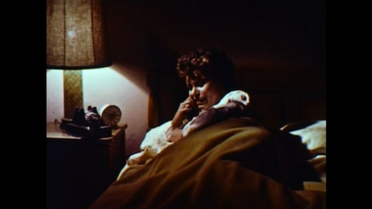United States: 1960s: lady in bed talks on phone. Man talks on phone. Men at station talk on phone. Sheets on line.