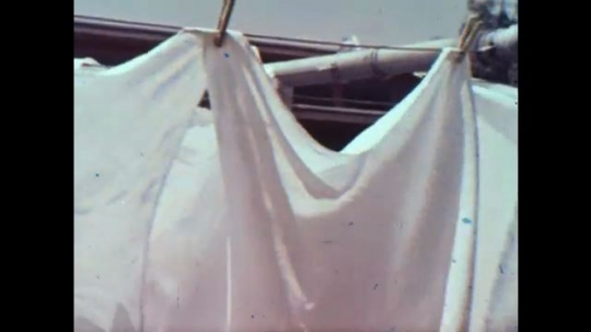 United States: 1960s: washing on line. Lady hangs diapers on line. People attend baby christening. People leave church.
