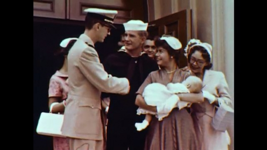 United States: 1960s: Lady stands with baby on steps. People gather after christening. Man walks with boy in garden.