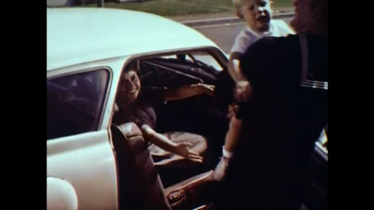 United States: 1960s: man hands baby to lady in car. Sailor, wife, and child visit show home. Lady hands baby to sailor.