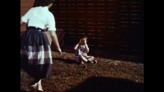 United States: 1960s: boy cries in garden. Lady rushes to boy. Lady comforts boy. Ladies move boy. Lady gets in car. Lady in drive way