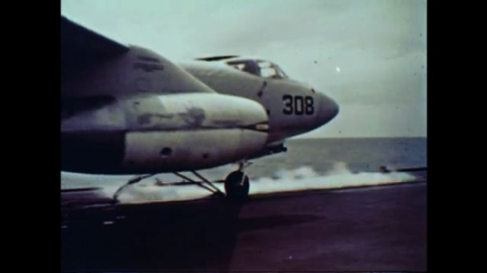 United States: 1960s: fast jet takes off from deck of ship. Navy men on ship deck. Plane lands on ship. Missile fired from ship. American flag on ship